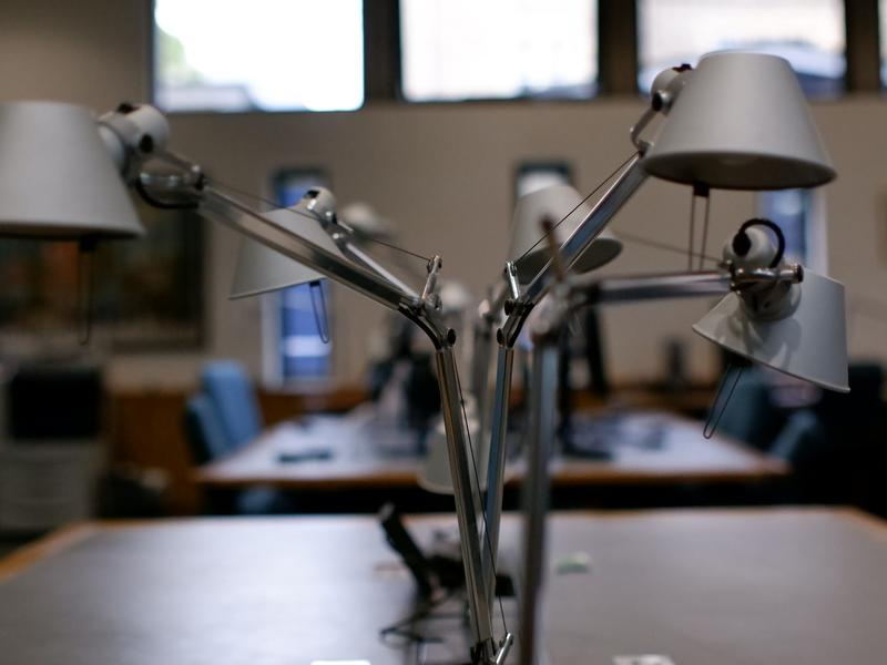 two silver metallic lamps on a desk