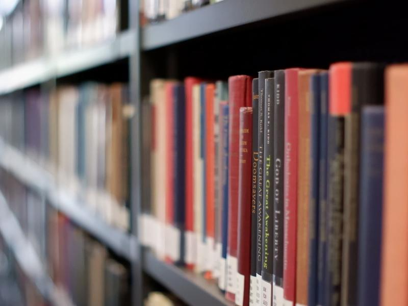 a row of books on a shelf in the library
